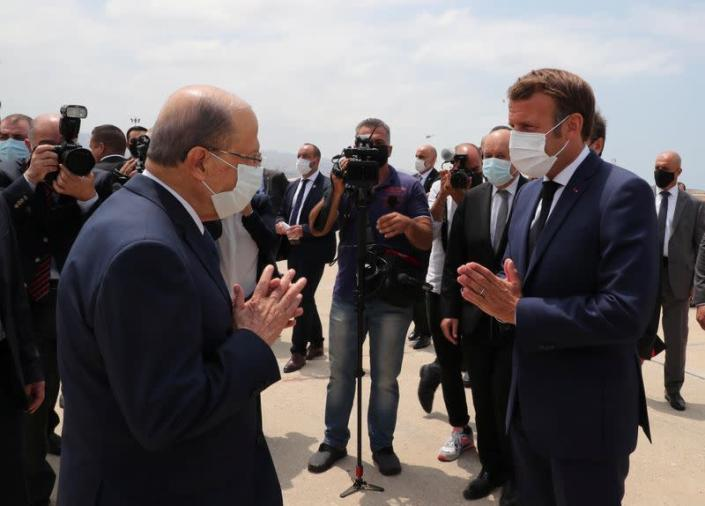 Lebanon's President Michel Aoun welcomes French President Emmanuel Macron upon his arrival at the airport in Beirut