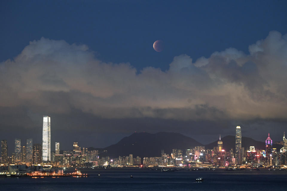 The moon rises over the Victoria Harbour in Hong Kong, Wednesday, May 26, 2021. The first total lunar eclipse in more than two years coincides with a supermoon this week for quite a cosmic show. (AP Photo/Kin Cheung)