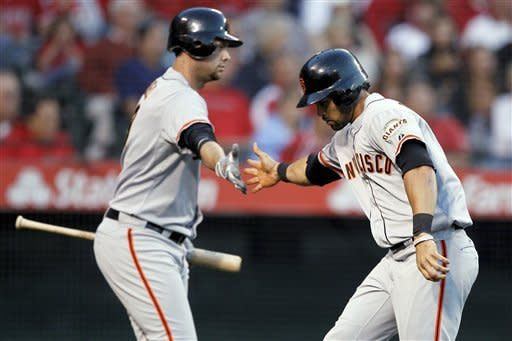 San Francisco Giants' Angel Pagan, right, celebrates with Brandon Belt after scoring on a single by Pablo Sandoval against the Los Angeles Angels during the second inning of a baseball game in Anaheim, Calif., Tuesday, June 19, 2012. (AP Photo/Chris Carlson)