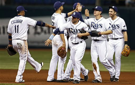Members of the Tampa Bay Rays, including, from left, Yunel Escobar, James Loney, Sam Fuld, Kelly Johnson and Evan Longoria celebrate a win over the Toronto Blue Jays in a baseball game Wednesday, May 8, 2013, in St. Petersburg, Fla. The Rays won 10-4. (AP Photo/Mike Carlson)