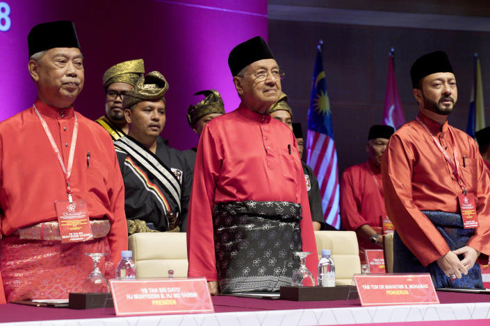 FILE- In this Dec. 29, 2018, file photo, Malaysian Prime Minster Mahathir Mohamad, center, stands next to his son Malaysian United Indigenous Party Vice President Mukhriz Mahathir, right, and President Muhyiddin Yassin, left, during the Malaysian United Indigenous Party general assembly at Putrajaya International Convention Centre in Putrajaya, Malaysia. Bersatu party said in a statement Friday, Feb. 28, 2020 that 36 lawmakers, including nearly a dozen who defected from Anwar Ibrahim's party, have decided to support party President Muhyiddin Yassin instead of Mahathir as prime minister. (AP Photo/Yam G-Jun, File)