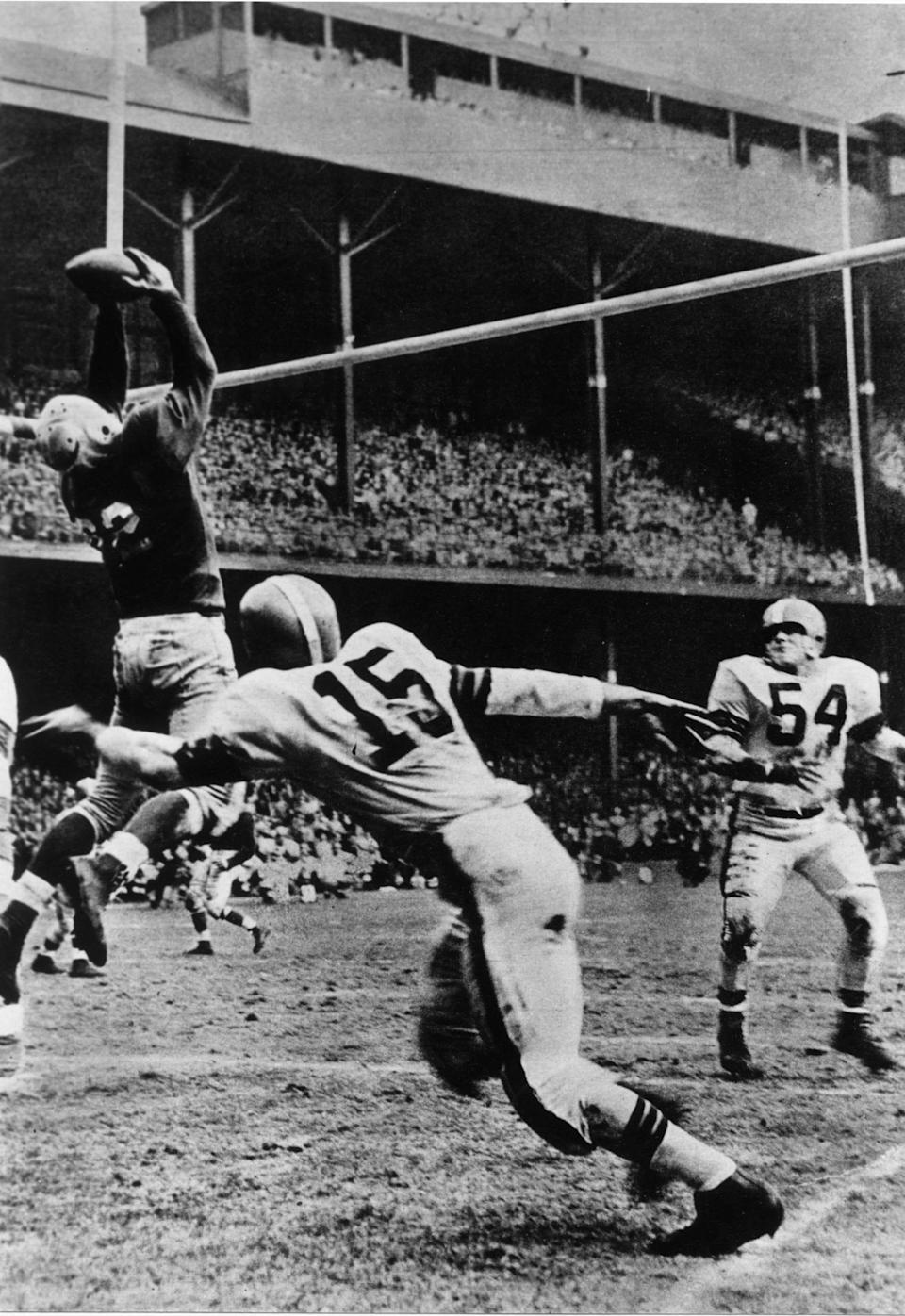 Lions quarterback Bobby Layne attempted to throw the ball out of bounds but Leon Hart, Lions #85, jumped up and caught it after it came over the cross bar for a touch down in game against the Cleveland Browns circa 1951-53.