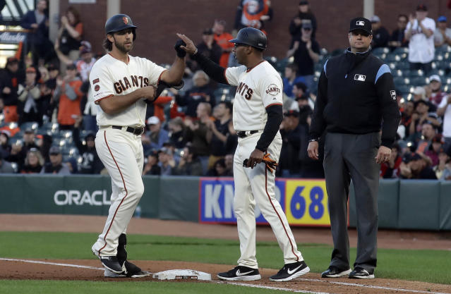San Francisco Giants' Madison Bumgarner, left, is congratulated by first base coach Jose Alguacil after hitting an RBI single against the Colorado Rockies during the fourth inning of a baseball game in San Francisco, Tuesday, June 25, 2019. (AP Photo/Jeff Chiu)