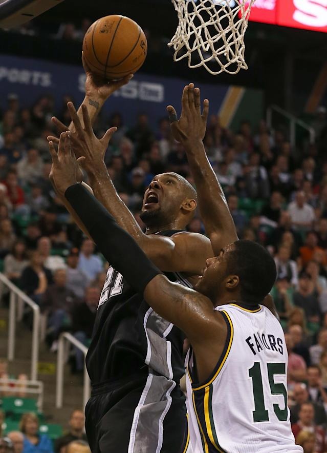 San Antonio Spurs Tim Duncan, top, shoots over Utah Jazz's Derrick Favors during the first half of an NBA basketball game in Salt Lake City, Friday, Nov. 15, 2013. (AP photo/George Frey)