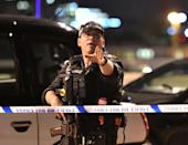 <p>An armed officer gestures to public as incident unfolds (Press Association) </p>