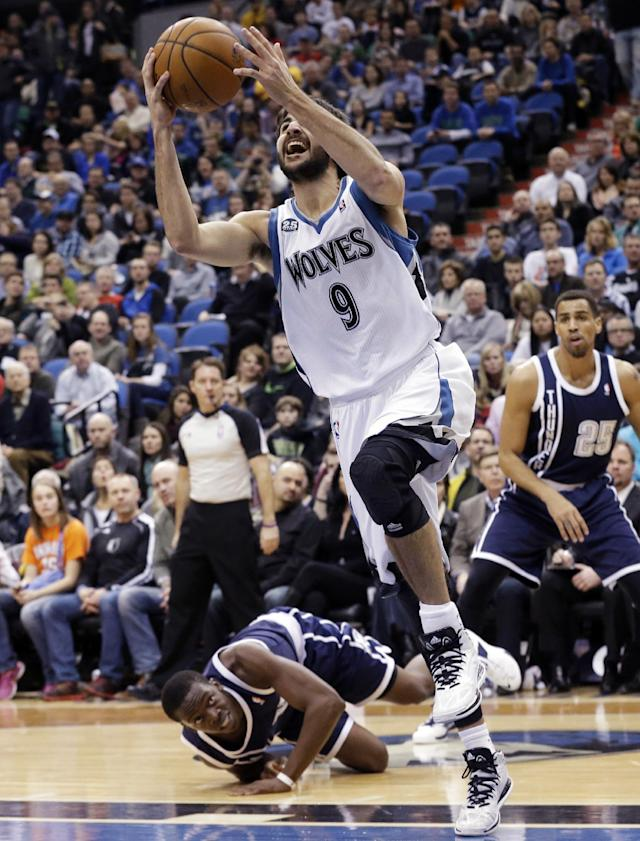 Minnesota Timberwolves' Ricky Rubio (9) eyes the basket as Oklahoma City Thunder's Reggie Jackson watches from the floor during the first quarter of an NBA basketball game Saturday, Jan. 4, 2014, in Minneapolis. (AP Photo/Jim Mone)