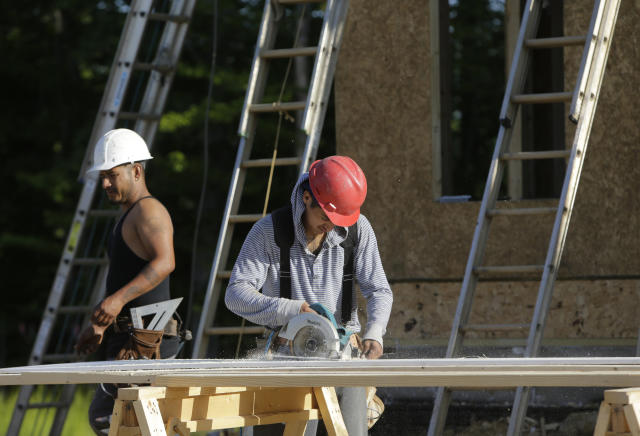 """Carpenters cut fascia trimwork at a housing site at Mid-Atlantic Builders """"The Villages of Savannah"""" development in Brandywine, Maryland May 31, 2013. REUTERS/Gary Cameron"""