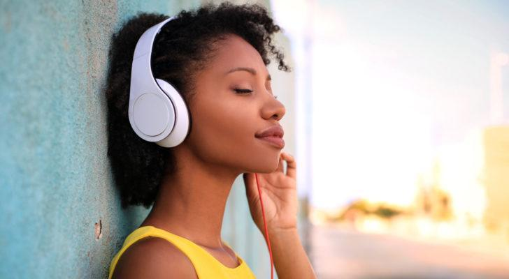 A woman listens to music on headphones while standing against a wall in an outdoor environment.