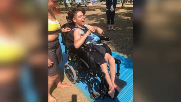 Bryce Vewchar and his mother Patricia Byziniak use the new access mat at Regina Beach. A group of local residents raised money to bring the mat and an accessible water wheelchair to the beach.  (Submitted by Janey Davies - image credit)