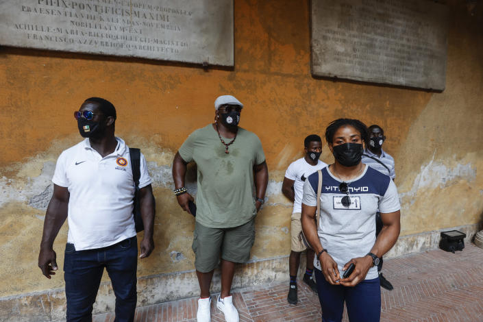 Freestyle wrestler Fatoumata Yarie Camara, of Guinea,foreground, pictured prior to receiving the COVID-19 vaccine at the Santo Spirito hospital in Rome, Saturday, July 3, 2021. In background, from left, United World Wrestling Development Officer Vincent Aka, of Ivory Coast, coach Alexis Rodriguez, of Cuba, and wrestlers Diamantino Fafe' and Augusto Midana, both from Guinea Bissau. A West African wrestler's dream of competing in the Olympics has come down to a plane ticket. Fatoumata Yarie Camara is the only Guinean athlete to qualify for these Games. She was ready for Tokyo, but confusion over travel reigned for weeks. The 25-year-old and her family can't afford it. Guinean officials promised a ticket, but at the last minute announced a withdrawal from the Olympics over COVID-19 concerns. Under international pressure, Guinea reversed its decision. (AP Photo/Riccardo De Luca)