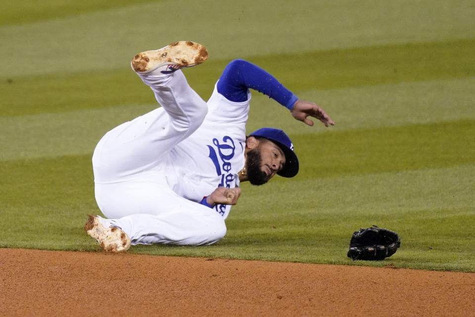 Los Angeles Dodgers third baseman Edwin Rios loses his glove after diving for a ball hit for a single by Cincinnati Reds' Jesse Winker during the fourth inning of a baseball game Monday, April 26, 2021, in Los Angeles. (AP Photo/Mark J. Terrill)