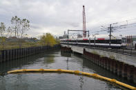 A train passes over a canal near the Hoboken Terminal in Hoboken, N.J., Tuesday, Oct. 27, 2020. The canal is part of a $200 million NJ Transit project to help prevent future flooding at Hoboken Terminal. (AP Photo/Seth Wenig)