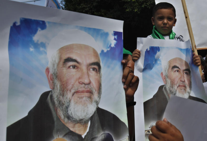 Palestinians carry pictures of Sheik Raed Salah, the leader of the Islamic Movement in Israel, during a protest to condemn what protesters claim was a desecration of Al-Aqsa Mosque in Jerusalem by Jewish extremists, in Gaza City, Wednesday, Sept. 4, 2013. Israeli police spokesman Micky Rosenfeld says that clashes in Jerusalem erupted Wednesday when some 300 Palestinian demonstrators tried to block a group of visitors from reaching the sensitive hilltop compound revered by both Jews and Muslims. Israeli police arrested seven Palestinians after clashes between stone-throwing demonstrators and Israeli security forces. (AP Photo/Adel Hana)