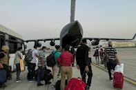 Indian Nationals prepare to board an Indian military aircraft at the airport in Kabul