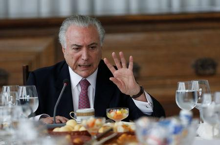 Brazil's President Michel Temer gestures during a breakfast with foreign media at Alvorada Palace in Brasilia