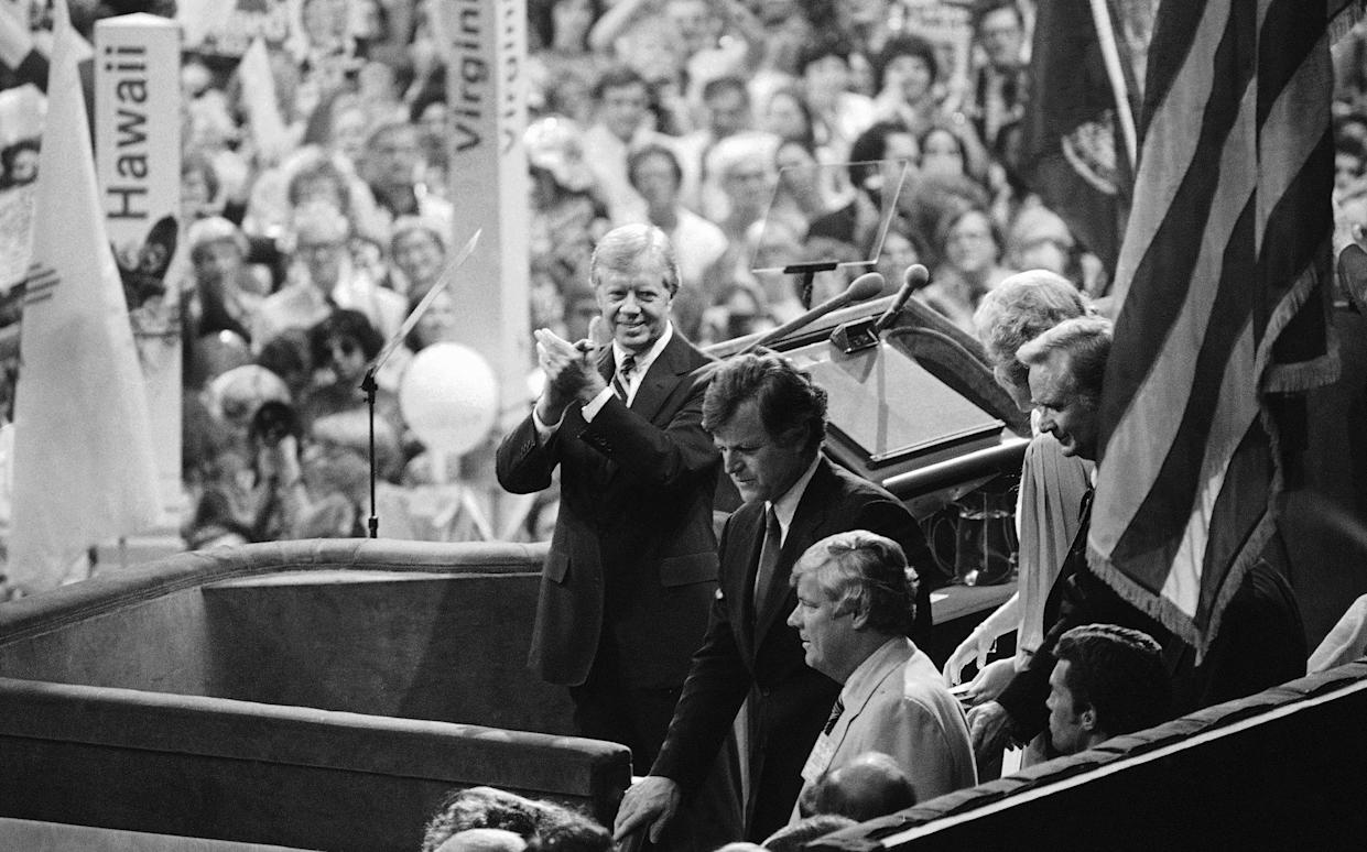 President Jimmy Carter applauds as Sen. Edward Kennedy waves to cheering crowds of the Democratic National Convention in New York's Madison Square Garden, Aug. 14, 1980. (Photo: Bob Daugherty/AP)
