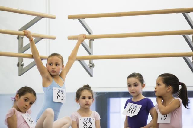 Children play on bars while waiting for their turn during an audition for the School of American Ballet in New York April 25, 2014. The school is holding auditions for over 600 beginner ballet students, who will be selected to fill the 120 spots available to study the dance on campus. REUTERS/Lucas Jackson (UNITED STATES - Tags: SOCIETY EDUCATION)