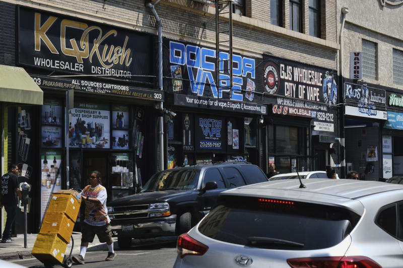 This Wednesday, Aug. 28, 2019, photo shows a bustling street lined with wholesale vape shops in downtown Los Angeles. A short walk from police headquarters in the heart of downtown, a cluster of bustling shops are openly selling packaging and hardware that can be used to produce counterfeit, and potentially dangerous, marijuana vapes that have infected California's cannabis market and possibly sickened dozens of people. (AP Photo/Richard Vogel)