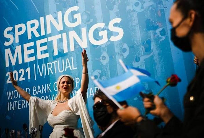 An activist dressed as Argentina's Evita Peron takes part in a rally calling for debt reform during the virtual Spring Meetings of the World Bank and International Monetary Fund