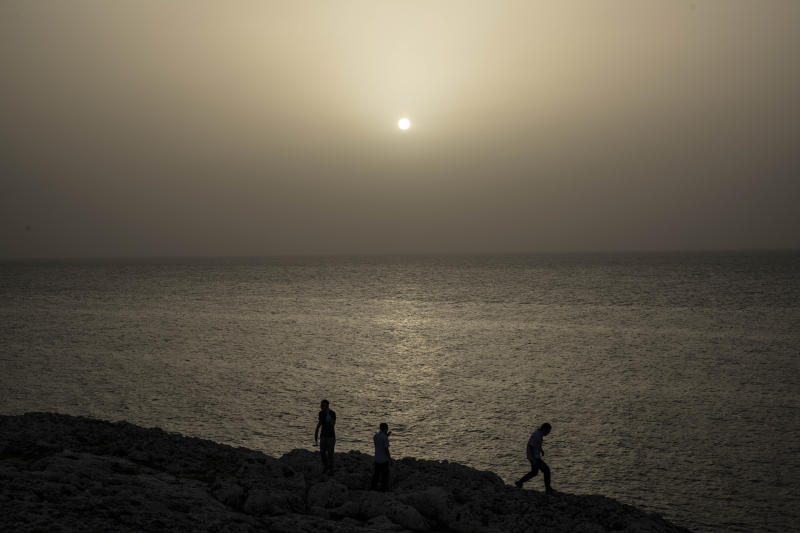 People watch the sunset while a cloud of Sahara dust hangs in the air in Havana on Wednesday, June 24, 2020. The massive cloud of dust is blanketing the Caribbean as it heads to the United States. (AP Photo / Ramon Espinosa)