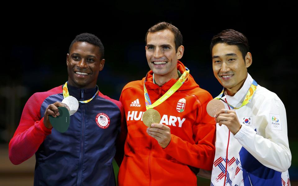 2016 Rio Olympics - Fencing - Victory Ceremony - Men's Sabre Individual Victory Ceremony - Carioca Arena 3 - Rio de Janeiro, Brazil - 10/08/2016. Aron Szilagyi (HUN) of Hungary celebrates winning the gold medal with Daryl Homer (USA) of USA and Kim Jung-Hwan (KOR) of South Korea. REUTERS/Nacho Doce FOR EDITORIAL USE ONLY. NOT FOR SALE FOR MARKETING OR ADVERTISING CAMPAIGNS.