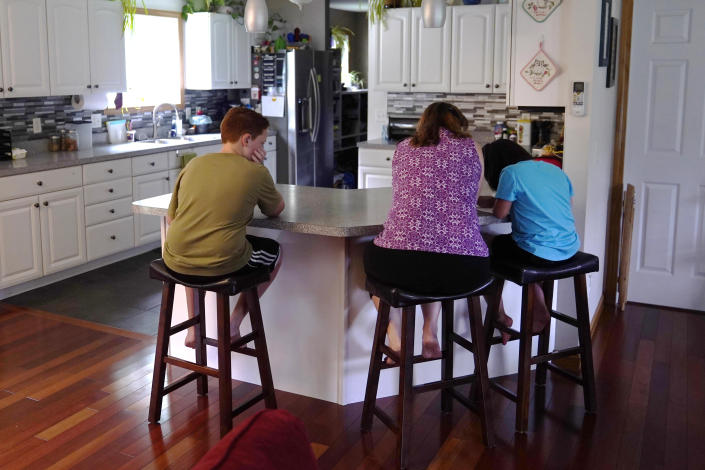 Jennifer Osgood, center, helps her children Lily, 7, right, and Noah, 12, left, while studying at the kitchen counter in the family's home, Tuesday, July 20, 2021, in Fairfax, Vt. The Osgood children will continue to be homeschool this upcoming school year. As the pandemic took hold across the United States in the spring of 2020, it brought disruption and anxiety to most families. Yet some parents are grateful for one consequence: they are now opting to homeschool their children even as schools plan to resume in-person classes. (AP Photo/Charles Krupa)