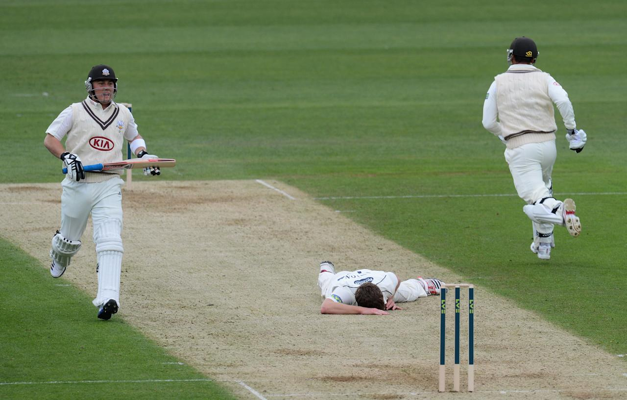LONDON, ENGLAND - APRIL 05:  James Anyon of Sussex slips after bowling as Rory Hamilton-Brown (L) and Zander de Bruyn of Surrey take a single during the LV County Championship match between Surrey and Sussex at The Kia Oval on April 5, 2012 in London, England.  (Photo by Mike Hewitt/Getty Images)