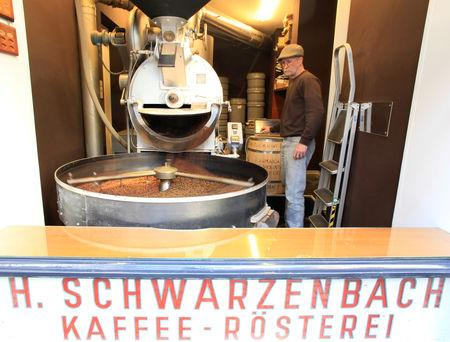 FILE PHOTO: Freshly roasted coffee beans fall into a tumbler after the drum type roaster is opened by an employee at H. Schwarzenbach coffee roastery in Zurich, Switzerland December 4, 2018. REUTERS/Arnd Wiegmann/File Photo