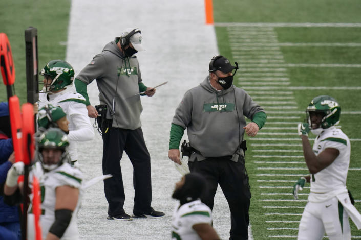 New York Jets head coach Adam Gase, center, checks his play sheet along the sideline in the first half of an NFL football game against the New England Patriots, Sunday, Jan. 3, 2021, in Foxborough, Mass. At right is special teams coordinator Brant Boyer. (AP Photo/Charles Krupa)
