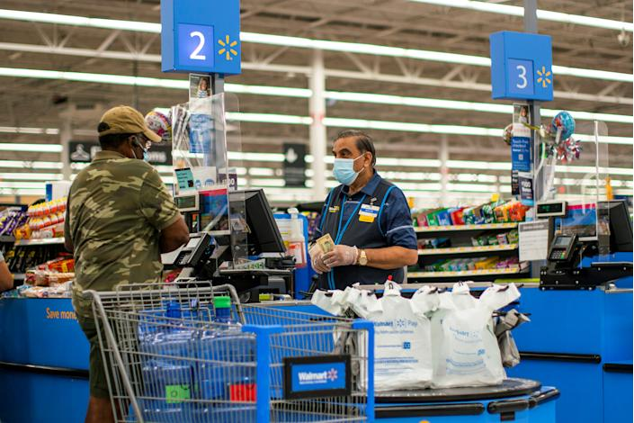 A worker and a shopper are seen wearing masks at a Walmart store, in North Brunswick, New Jersey, U.S. July 20, 2020. REUTERS/Eduardo Munoz