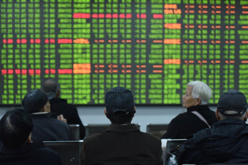 Investors sit in front of a board showing stock information at a brokerage house on the first day of trade in China since the Lunar New Year, in Hangzhou