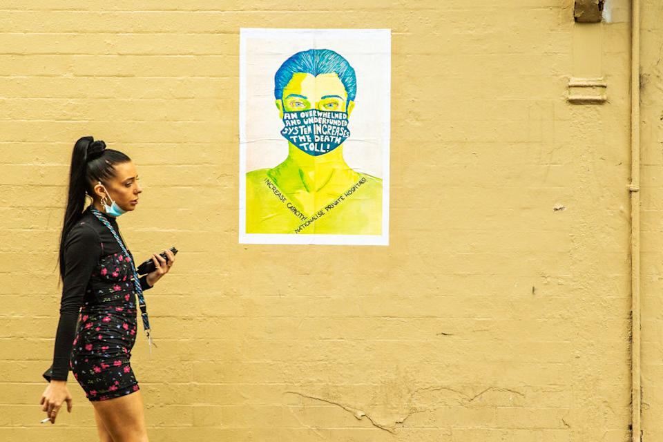 A woman is seen walking past a political poster in Sydney, Australia.