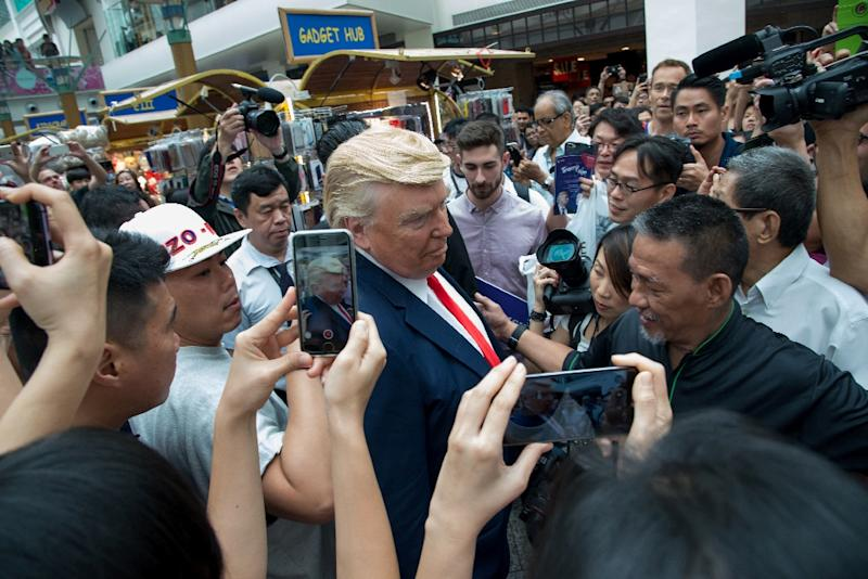 "Dubbed the ""real"" Trump-Kim summit, the men waved at shoppers as they walked through the crowded Bugis Junction mall for a promotional event (AFP Photo/TOH TING WEI)"
