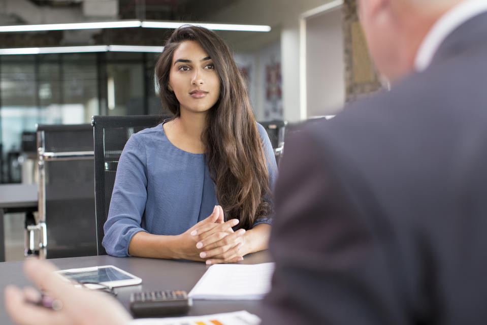 Focused Indian female customer meeting with financial advisor. Young beautiful candidate at job interview in modern office space. Business consulting or employment concept