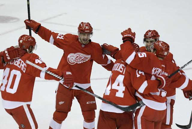 Detroit Red Wings left wing Tomas Tatar (21), of the Czech Republic, rushes in to celebrate the goal by defenseman Niklas Kronwall (55), of Sweden, during the third period of an NHL hockey game against the Los Angeles Kings in Detroit, Saturday, Jan. 18, 2014. (AP Photo/Carlos Osorio)