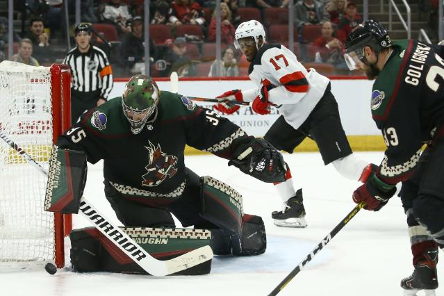 Arizona Coyotes goaltender Darcy Kuemper (35) makes a save on a shot as New Jersey Devils right wing Wayne Simmonds (17) and Coyotes defenseman Alex Goligoski, right, look on during the first period of an NHL hockey game, Saturday, Dec. 14, 2019, in Glendale, Ariz. (AP Photo/Ross D. Franklin)