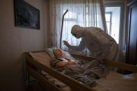 """Father Vasily Gelevan, a Russian Orthodox priest, blesses Lyudmila Polyak, 86, who is believed to be suffering from COVID-19, at her apartment in Moscow, June 1, 2020. Associated Press photographer Alexander Zemlianichenko says this of the image: """"I feel it's both very intimate and also deeply symbolic, an image of empathy and self-denial in the face of mortal danger."""" He says taking the photo was """"also very important for me on a personal level, an experience that transformed me, helping overcome my own fear"""" of the virus. (AP Photo/Alexander Zemlianichenko)"""