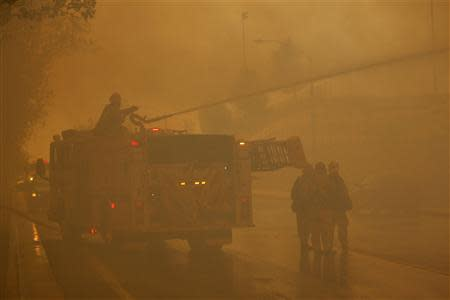 Firefighters protect homes as a wildfire driven by fierce Santa Ana winds blows in Rancho Cucamonga, California.