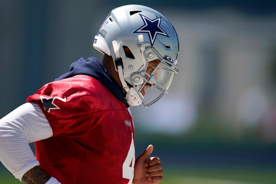 Dallas Cowboys quarterback Dak Prescott jogs onto the practice field for a workout at the team's NFL football training facility in Frisco, Texas, Wednesday, Aug. 25, 2021.