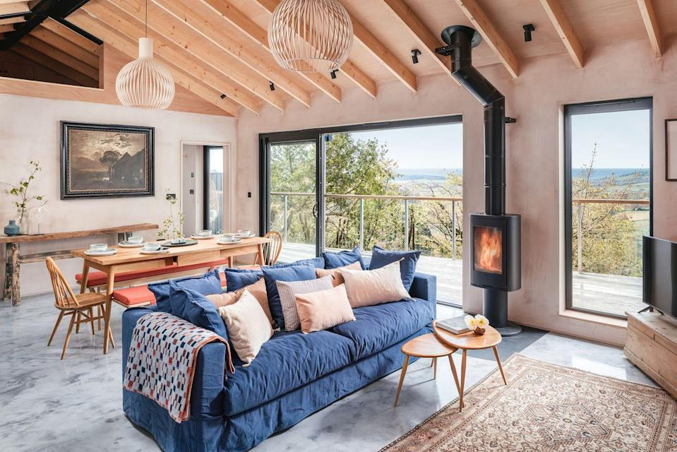 """<p>Nestled away on the hillside of a wooded valley, you'd be forgiven if you thought Fjall was a house from one of your favourite romcom films given its beauty, grandeur and award-worthy vistas. With views of Charmouth and the Jurassic Coast, the repurposed flint-stone fronted building serves as the perfect contrast to the site's modern wooden and pink-coloured plaster-patterned interiors, with its double-height lounge, handwoven textiles designed by the owner, standalone egg bathtub and rainfall shower. </p><p>There are floor-to-ceiling sliding doors from the lounge that take you out on the deck where you can watch the sun rise and fall, over breakfast or hot toddies, with the beach of Lyme Regis just a short drive away if you're in need of sand and ice cream. </p><p><strong>House for up to six guests from £1,550 per week</strong></p><p><a class=""""link rapid-noclick-resp"""" href=""""https://www.uniquehomestays.com/unique-escapes/new-and-coming-soon/uk/dorset/lyme-regis/fjall/"""" rel=""""nofollow noopener"""" target=""""_blank"""" data-ylk=""""slk:BOOK ONLINE"""">BOOK ONLINE </a></p>"""