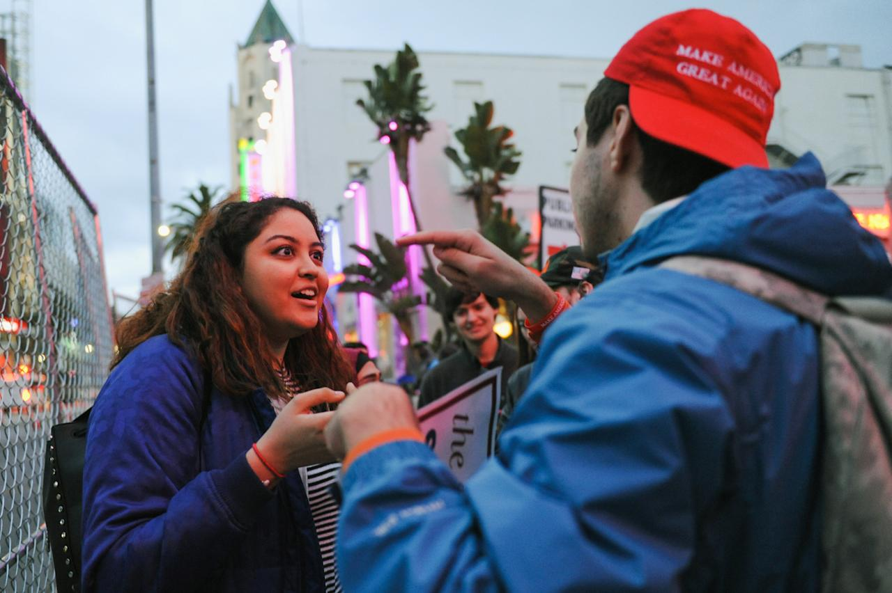 A Trump supporter points at Nazmun Nahar, a student at the University of Michigan who came to Los Angeles with friends for spring break, as they argue outside the Oscar ceremony, in Hollywood, California, U.S. February 26, 2017. REUTERS/Andrew Cullen