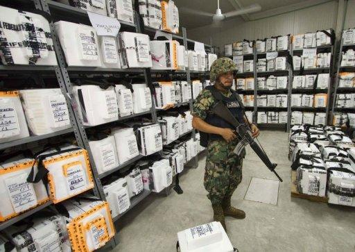 A Mexican marine stands guard inside the Federal Electoral Institute (IFE) building during the counting of votes from the presidential election in Acapulco, Guerrero state, Mexico. Mexico's national election authority announced a recount of ballots cast at more than half of the polling stations in the country's weekend presidential election in which Enrique Pena Nieto claimed victory