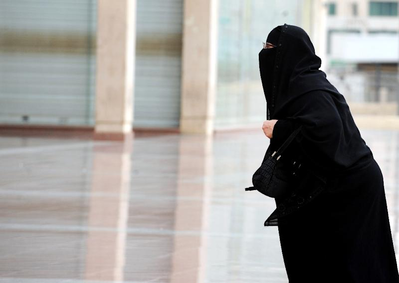 A fully-veiled Saudi woman walks into a mall in Riyadh on November 19, 2012