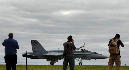FILE PHOTO: Spectators watch as a Boeing F/A-18E/F Super Hornet fighter plane belonging to the Royal Australian Air Force lands during the Australian International Airshow in Melbourne, Australia March 2, 2011.   REUTERS/Mick Tsikas/File Photo