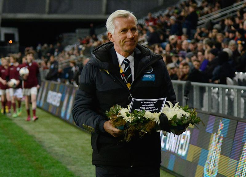 Newcastle United coach Alan Pardew carries a wreath in memory of two fans who lost their lives in the Malaysia Airlines flight MH17 crash, during the match between Sydney FC and Newcastle United at the Forsyth Barr Stadium in Dunedin on July 22, 2014