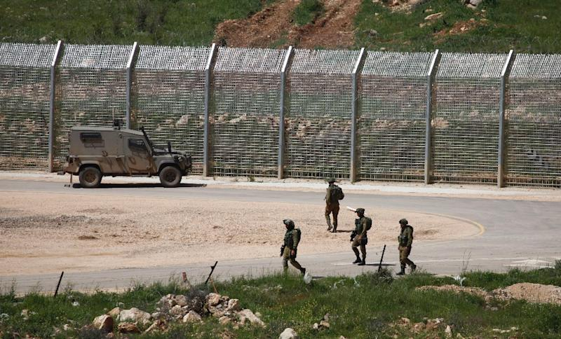 Israeli soldiers walk near a fence in the Israeli occupied Golan Heights on the border with war-torn Syria, on April 27, 2015 (AFP Photo/Jalaa Marey)