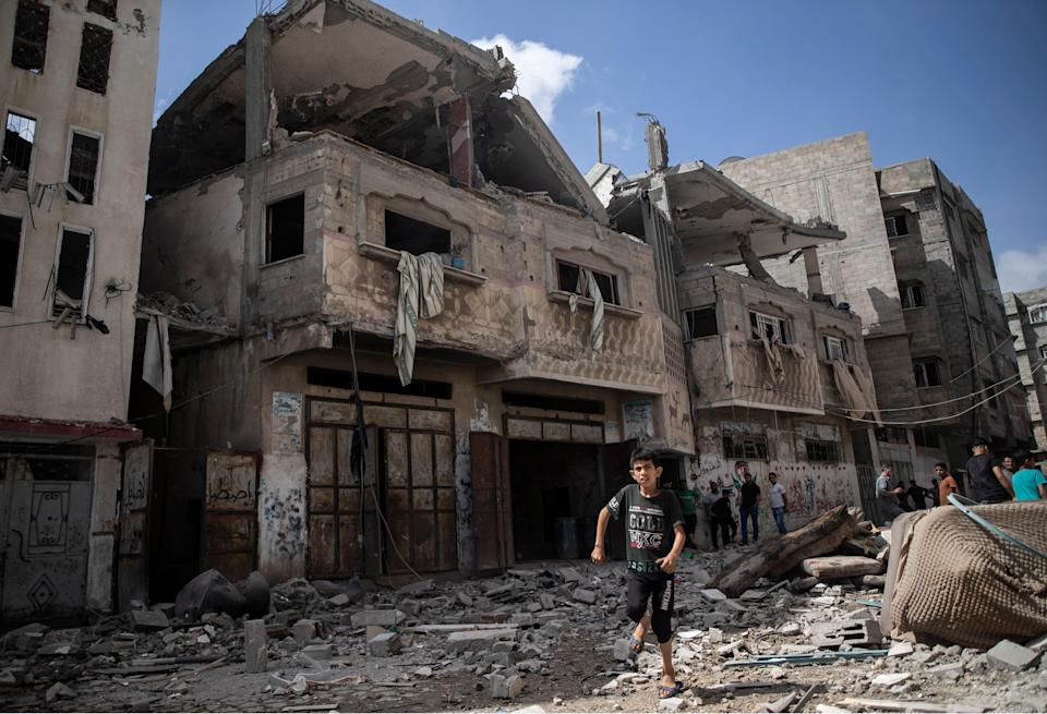 Palestinians inspect damaged houses that were hit in early morning Israeli airstrikes, in Gaza City (AP)