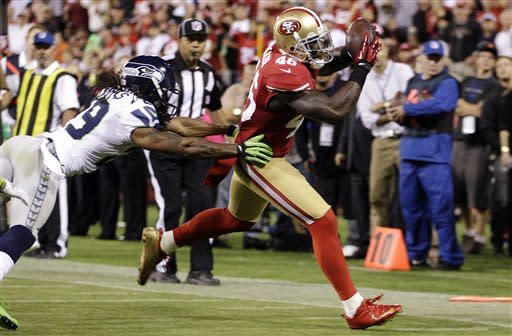 San Francisco 49ers tight end Delanie Walker (46) scores on a 12-yard touchdown reception past Seattle Seahawks free safety Earl Thomas (29) during the third quarter of an NFL football game in San Francisco, Thursday, Oct. 18, 2012. (AP Photo/Ben Margot)