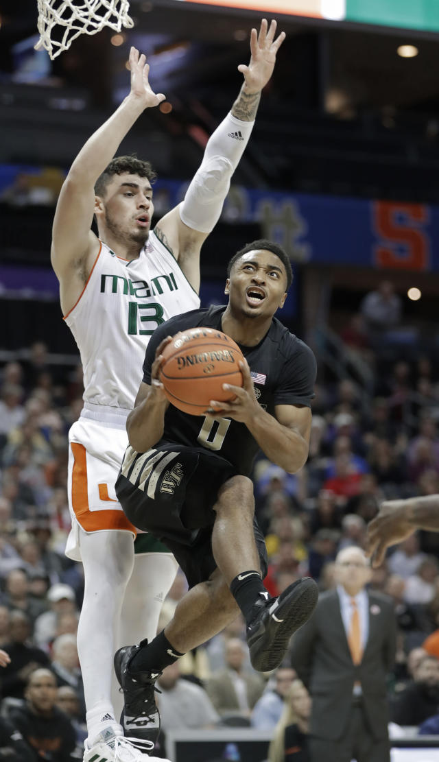 Wake Forest's Brandon Childress (0) drives past Miami's Anthony Mack (13) during the first half of an NCAA college basketball game in the Atlantic Coast Conference tournament in Charlotte, N.C., Tuesday, March 12, 2019. (AP Photo/Nell Redmond)