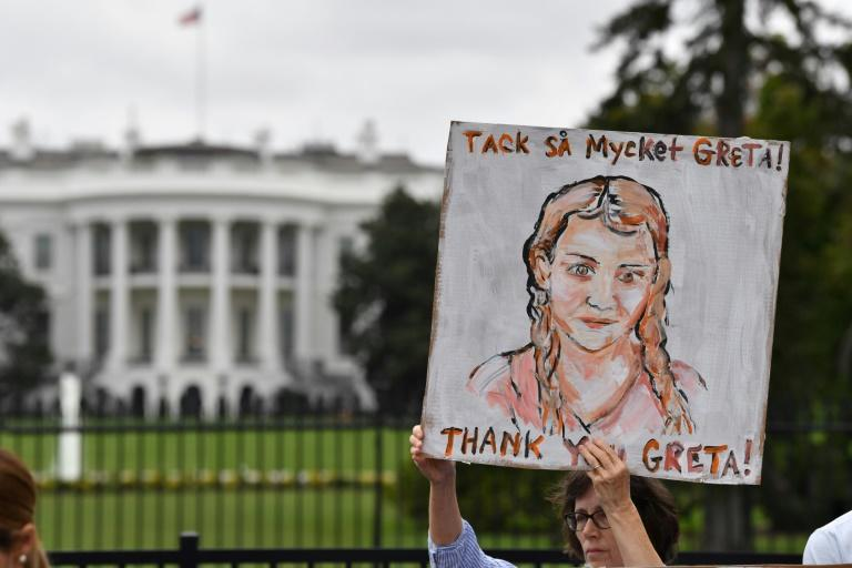A woman holds up a poster depicting Swedish environment activist Greta Thunberg, during a climate protest outside the White House